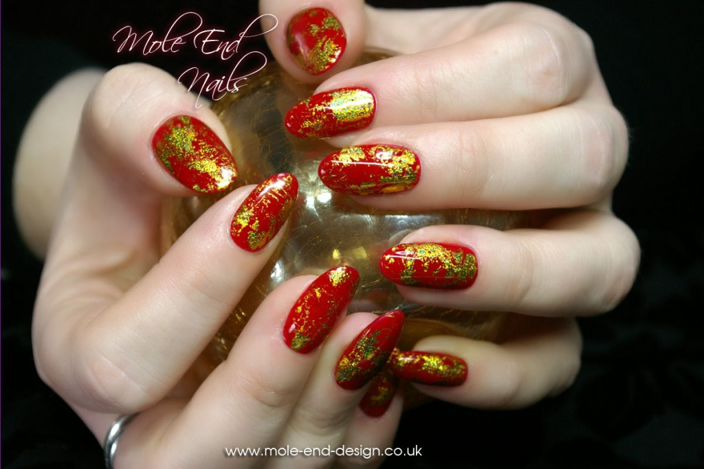 Red nails with gold foil accents