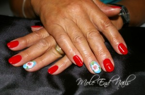 Red nails with hand painted floral accents