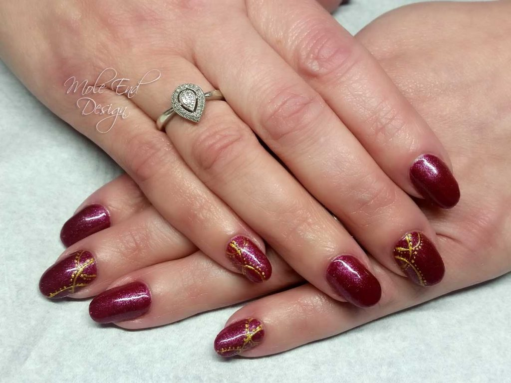 Red gel polish with gold lines